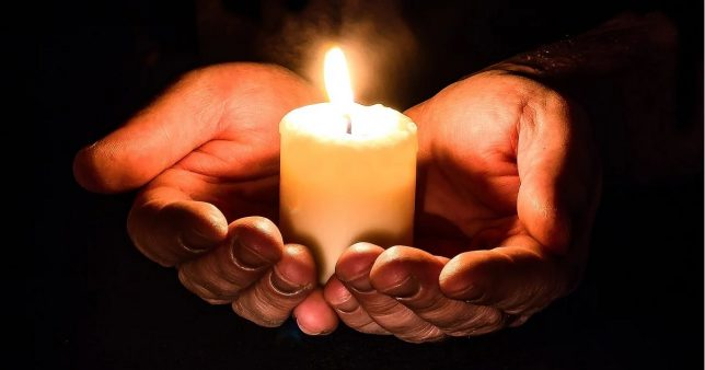 picture of a person holding a lit candle depicting protection and life insurance which is the subject of the article