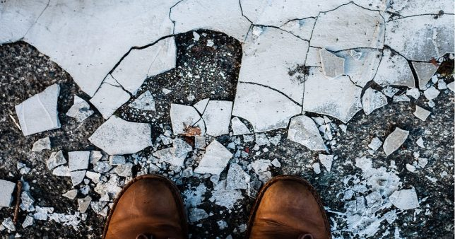 image of a man standing before broken tiles representative of the broken SEBI's proposed regulations that could kill off fee only financial planning and Jack Bogle's legacy