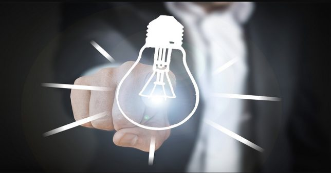 Image of a glowing light bulb with a person pointing to it representing an idea of how to use mutual funds stock losses to reduce your tax burden (tax-loss harvesting)