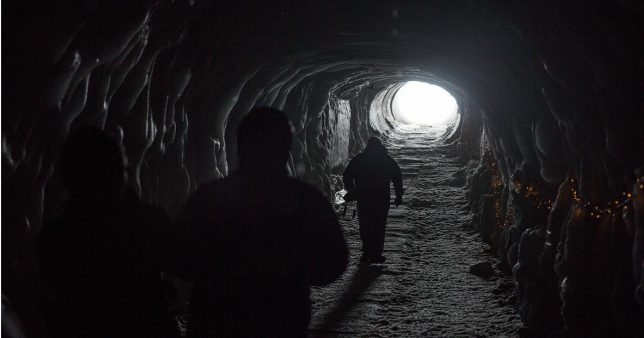 Image of people travelling towards light at the end of a tunnel reflecting the mindset of those who prepare for layoff and job loss with proper money management