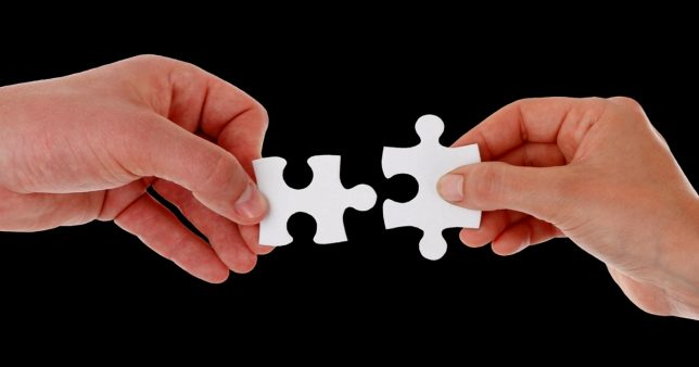 Image of two hands trying to join puzzle pieces representing the dispute settlement movtive behind the Direct Tax Vivad se Vishwas Scheme (DTVSV) 2020