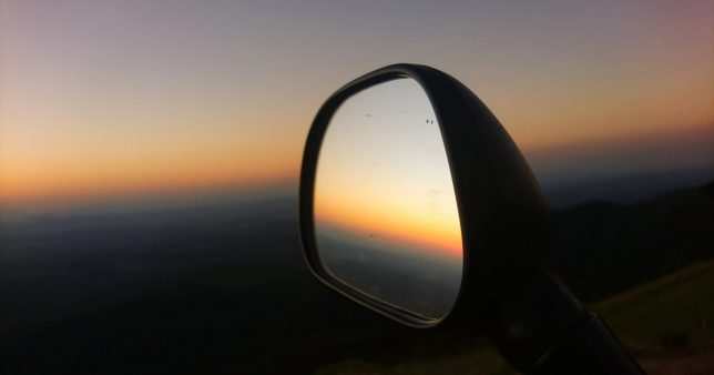 Image of a sunset with a reflection in the rear-view mirror of a car representing how the 2020 debt fund crisis is a repeat of 2008