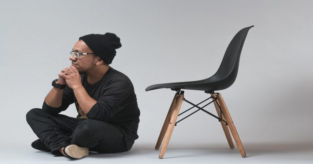 image of a man sitting down with a chair next to home as if to suggest he is out of work and thinking about how to generate an income for the next couple of years