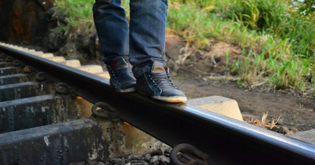 image of a person walking on rails indicating the tracking error of an index fund