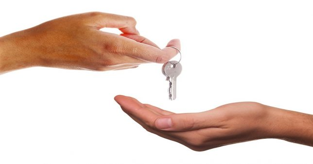 Image of a person giving property keys to heirs as part of proper legacy planning