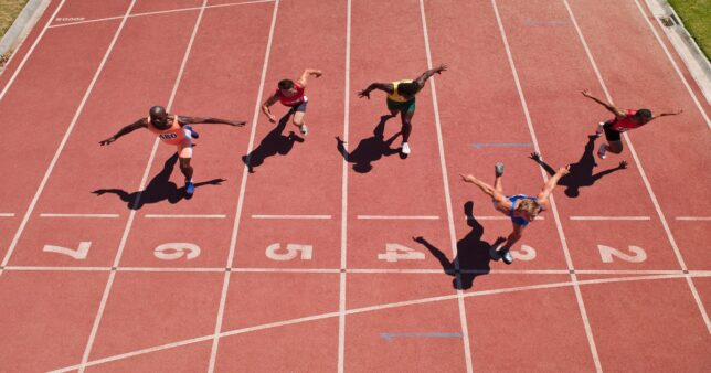 Athletes competing a race at the finish list representing Nifty index funds trying to track the index as efficiently as possible